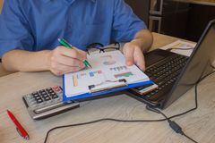Home finances, investment, economy. person Man pointing writing goals on a paper,writing business plan at workplace, man holding p. Ens, papers, notes in royalty free stock images