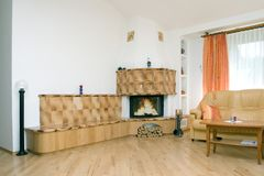 Home fireplace. Fireplace in beige with white walls at home. brown chairs ad fire wood Stock Photography