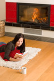Home fireplace happy woman read book winter Royalty Free Stock Image