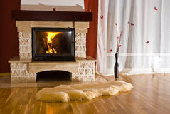 Home fireplace and rug. A cozy view of a warm fire burning in a home fireplace with a thick, fleecy throw rug on the hardwood floor in front Stock Images