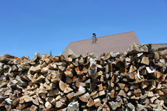 Home firewood. Pile of chopped firewood with a roof in the background Stock Images