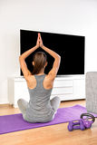 Home fitness woman doing yoga exercise watching tv. Yoga girl doing meditation exercise in living room at home. Woman watching fitness dvd workouts or streaming Royalty Free Stock Image