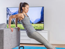 Home fitness woman training on living room sofa. Home fitness woman strength training arms watching online tv dvd workouts doing bodyweight exercises in living Stock Photography