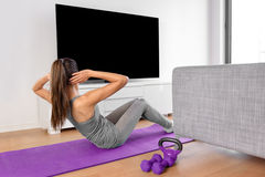 Home fitness woman watching workout videos on tv. Home fitness concept. Woman doing strength training abs situps bodyweight floor exercises watching a dvd Royalty Free Stock Photo