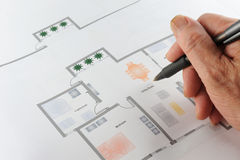 Home floor plan. Colorful home floor plan with a hand holding a pen on it, three rooms,one living room royalty free stock photo