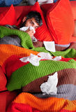 At Home with the Flu and Kitty. A man at home with the flu. He's wrapped up in a blanket on the couch with his cat and tissue paper Stock Photo