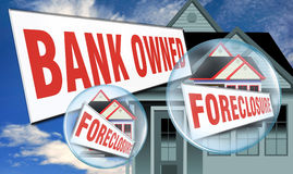 Home foreclosed by bank. Property, somebody's home, superposed with with large signs in bold upper case red text saying ' foreclosure ' and ' bank owned ' Royalty Free Stock Photography
