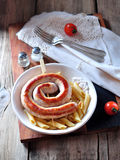 Home fried sausage with boiled pasta in olive oil on old wooden background. Stock Photo