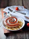 Home fried sausage with boiled pasta in olive oil on old wooden background. Stock Photos