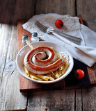 Home fried sausage with boiled pasta in olive oil on old wooden background. Royalty Free Stock Photography