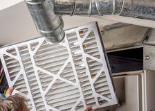Home Furnace filter inspection for dirt. Handyman inspects a filter from a home furnace Royalty Free Stock Images