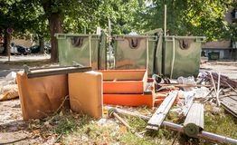 Home furniture thrown in the garbage on the street in the city near plastic dumpster cans littering and polluting the town and env. Ironment stock image