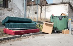 Home furniture thrown in the garbage on the street in the city near plastic dumpster cans littering and polluting the town and env. Junk on the city street, Home stock photos