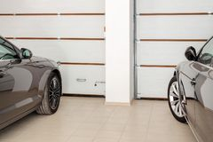 Home garage for two vehicles interior. Clean luxury cars parked at home. Automatic remote control doors. Transport roofed storage.  Stock Photos
