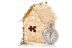 Home of gold color puzzles with a stopwatch Royalty Free Stock Images