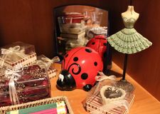 Home Goods: Shelves With Home Decoration Products. Home decoration items: ladybug money bank, heart shaped metal box on a wooden box, mirror, flower painting Stock Photo