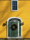 Home: green door and one window. New England yellow house with green door, one window and a Christmas wreath Stock Photography