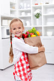 Home with the groceries. Happy healthy girl with apron in the kitchen holding groceries bag Stock Images