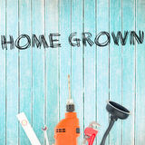 Home grown against tools on wooden background Royalty Free Stock Image