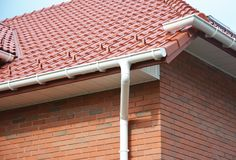 Home Guttering, Roofing Construction, Gutters, Plastic Guttering System, Roof  Tiles, Guttering & Drainage Pipe House Building. Close up on House Problem Areas Stock Photography
