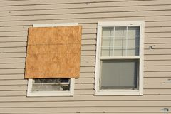 Home Hail damage. Boarded up window and hail storm damage on house siding and window frame royalty free stock photo