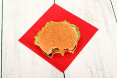 Home hamburger with a small bite. Homemade hamburger with fresh vegetables on wooden table, top view Royalty Free Stock Images
