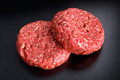 Home HandMade Raw Minced Beef steak burgers on black board.  Royalty Free Stock Images