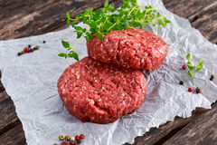 Home HandMade Raw Minced Beef steak burgers on scrumbled paper Royalty Free Stock Photo