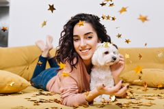 Home happy moments with pets young beautiful woman with cut brunette curly hair having fun in golden tinsels on couch in. Home happy moments with pets of young stock photography