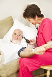 Home Health - Blood Pressure Vertical. Home health nurse taking an elderly patient's blood pressure.  Vertical view Stock Images