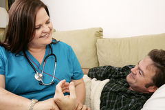 Home Health Care. Kind, friendly home health nurse taking her patient's pulse. Both are smiling royalty free stock photos