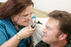 Home Health - Eye Exam. Home health nurse checking her patient's eyes with an ophtalmoscope stock photos