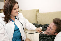 Home Health - Friendly Nurse. Friendly home health care nurse listing to her patient's chest with a stethoscope Royalty Free Stock Photo