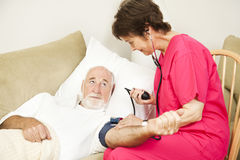 Home Health Nurse Takes Blood Pressure. Home health care nurse taking a senior patient's blood pressure Royalty Free Stock Image