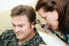 Home Health - Otoscope. Home health nurse using an otoscope to look in her patient's ears royalty free stock images