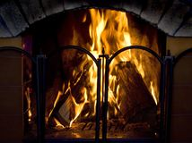 Home hearth. Burning flame in fireplace with fireguard, focus on firewoods Royalty Free Stock Photos