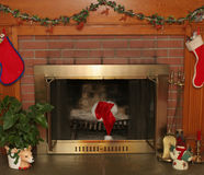 Home and Hearth. Fireplace in home decorated for christmas with a sant hat left behind sitting atop logs in fireplace Stock Photography