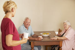 Home Help Sharing Cup Of Tea With Senior Couple In Kitchen Royalty Free Stock Photography