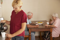 Home Help Sharing Cup Of Tea With Senior Couple In Kitchen Stock Images