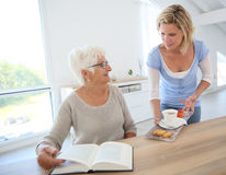 Home helper bringing tea and cookies to elderly Stock Photos