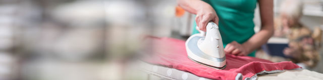 Home helper ironing clothes for an old woman. Home helper ironing clothes for elderly woman royalty free stock images