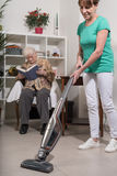 Home helper vacuuming for an old woman Royalty Free Stock Photography