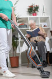Home helper vacuuming for an old woman Royalty Free Stock Image