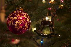 Home for the Holidays. Hand painted globe and reindeer Christmas tree ornaments hung on a Noble Fir tree Stock Image