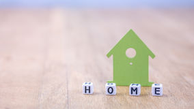 HOME horizontal word of cube letters behind green house symbol on wooden surface Royalty Free Stock Images
