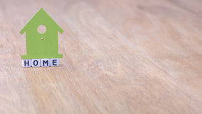 HOME horizontal word of cube letters with green house symbol above on wooden surface Royalty Free Stock Photos