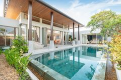 Home or house building Exterior and interior design showing tropical pool villa with green garden stock image
