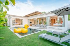 Home or house Exterior design showing tropical pool villa with greenery garden, sun bed and floating duck royalty free stock images