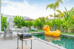 Home or house Exterior design showing tropical pool villa with greenery garden, sun bed and floating duck stock photo
