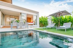 Home or house Exterior design showing tropical pool villa with greenery garden, sun bed, umbrella, pool towels stock image